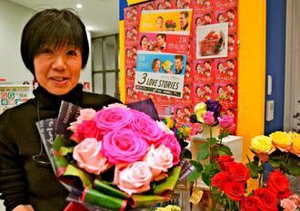 バレンタインデーに向け用意している花束を手にする伊藤由里さん。店内にポスターを張り、雰囲気を盛り上げている=北中城村・太陽の花アンテナショップ「マカロン」