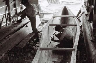 1935年の説明に「ノミを使って造られる刳舟(くりぶね)」とある1枚。工房の両端には板材が立てかけられており、刳舟といっても丸木をくりぬく「丸木舟(マルキンニ)」ではなく、板材を張り合わせる「接ぎ舟(ハギンニ)」であると分かる。漁法や何人用か、イノーの内、外のどちらで使うかなどで職人の数だけ特徴が異なるとされた。同年は日露戦争(1904~05)から30年の節目で、旧海軍がバルチック艦隊を発見した山原船の船頭、サバニで急報を伝えた5人の計6人を「沖縄六勇士」(大阪朝日新聞、同年2月25日など)として表彰し、軍の宣伝に使った。サバニに乗った漁師は、沖縄戦でも切り込み隊や伝令にされた(写真はいずれも朝日新聞提供)