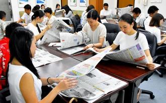 真剣な表情で新聞を読む受講者=13日、那覇市・JTA本社