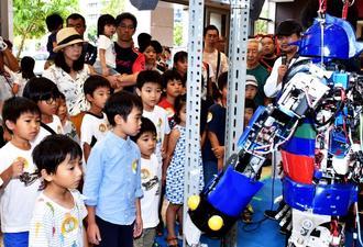 人間に連動して動くロボットに興味津々の子どもたち=11日、那覇市・タイムスビル