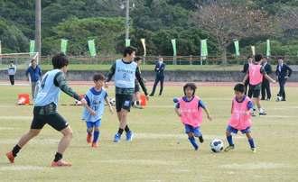 ミニゲームで交流するヴァンラーレ八戸の選手と地域の子どもたち=10日、本部町運動公園陸上競技場