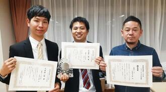 賞状を受け取った(右から)伊集竜太郎記者、比嘉太一記者、西倉悟朗記者=22日、東京・台東区民会館