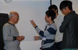 起業家の熊谷芳太郎さん(左)に質問するRyukyufrogsのメンバーら=20日、プラグアンドプレイテックセンター