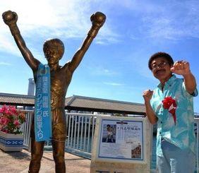 国際ボクシング殿堂入りのパネルの前でポーズを取る具志堅用高さん=22日、石垣港離島ターミナル