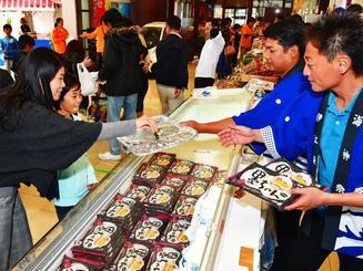 連日完売の人気商品「イカ墨ぎょうざ」を試食する来場者=22日、那覇市久茂地・タイムスビル