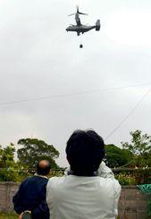 住宅の真上や真横を低空でつり下げ訓練するオスプレイ。住宅の敷地内で見ていた沖縄防衛局職員(奥)はそのたびに住民に謝罪していた=12月6日、宜野座村城原区