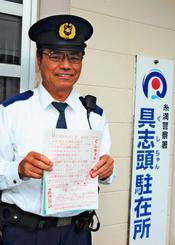 しまくとぅばを交えて作成した警察広報を手に笑顔を見せる小渡鍚幸巡査部長=9日、八重瀬町玻名城・糸満署具志頭駐在所