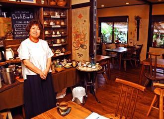 店主の喜瀬文子さんと、木製の調度品が温かみを添える店内。ドリンクセットのカップは客が好みで選べる