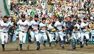 甲子園春夏連覇を果たし、笑顔でアルプス席に向かって駆け出す興南ナイン=2010年8月21日、甲子園球場