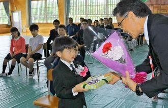 儀間校長から入学記念品を受け取る山名元太君(左)=7日、鳩間小中学校