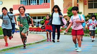 台風の影響で給食がなく、昼過ぎに下校する児童たち=12日午後0時半ごろ、豊見城市高安・とよみ小学校