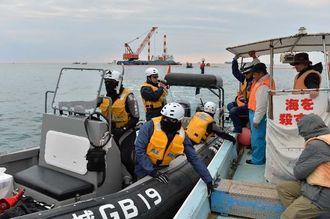 作業船から遠ざけるため、抗議船(右)をえい航する海上保安官=2日午前9時、名護市の大浦湾