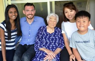 県内で高齢者の写真を撮っているジュランドさん(左から2人目)と妻のシャンティさん(左端)、モデルになった饒平名さん(中央)と仲介した山本麻紀さん、琥太郎君=4月23日、本部町・饒平名さん宅