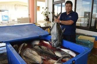 15~20キロ近いガーラを手に大漁を喜ぶ金城肇組合長=27日午前、読谷村の都屋漁港
