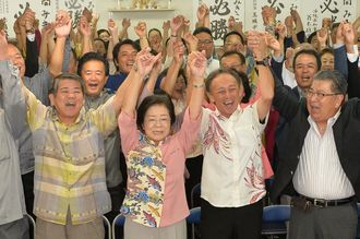 再選を確実にし、支持者らとバンザイで喜ぶ城間幹子氏(中央)=21日午後8時2分、那覇市松山の選挙事務所(古謝克公撮影)