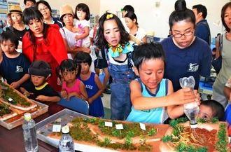 模型の上流に水を注ぎ込み、赤土が流出する仕組みを体験する子どもたち=大浜公民館