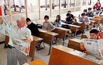 就職活動を控えた学生に新聞の活用法を助言する樋口克次さん(左)=12月19日、宜野湾市の沖縄国際大学