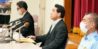 記者会見で容疑者逮捕について発表する県警の崎原永克刑事部長(中央)=26日午後9時16分、豊見城署