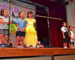 学校を支える人々にふんし、しまくとぅばで発表する城北小学校1年4組の児童ら=那覇市首里、石嶺公民館