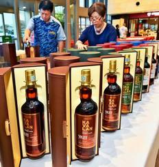 台湾の高級ウイスキーを並べ、開幕準備を進める関係者=20日、那覇市・タイムスビル