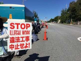 「違法工事中止」のプラカードを掲げ新基地建設反対を訴える市民=15日午前8時半、名護市辺野古