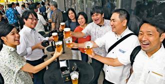「パーフェクトデイズ2019」で乾杯する来場者=21日午後、那覇市久茂地・タイムスビル