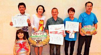 第2回宮古島うまむぬ杯でグランプリを獲得した、たまご家「おかん」の神原紀美代さん(後列左から2人目)、店主の知明さん(中央)=10月28日、JTAドーム宮古島