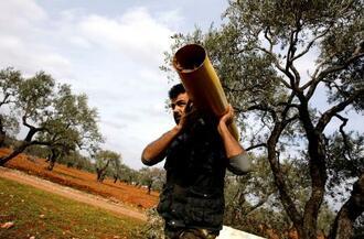 シリア反体制派最後の拠点、北西部イドリブ県で、砲弾の薬きょうを運ぶシリア人=27日(ロイター=共同)