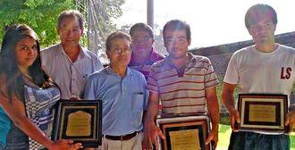 学事将来会で記念版を送られた(右から)山里さん、平良さんと与那城さん(左端)=フロレンシオ・バレーラ日本人会会館