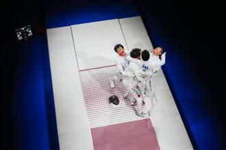 男子エペ団体で金メダルを獲得し、抱き合って喜ぶ日本チーム=幕張メッセ