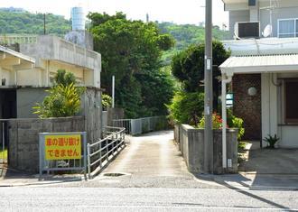 和仁屋(右側)と熱田の境界となる路地。車が通り抜けられないほどの細い道だ=5日、北中城村