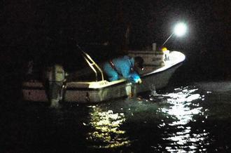 サメ捕獲のために入れた網を引き上げる漁業者=日午後9時ごろ、北谷町美浜