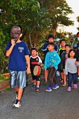 来訪神「パーントゥ」に扮した男の子を先頭に集落を練り歩き、厄を払う住民=28日夕、宮古島市上野野原