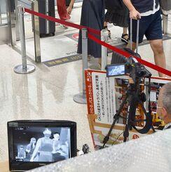 「Go To トラベル」が始まり、那覇空港でサーモグラフィーによる検温を受ける観光客ら=22日午前