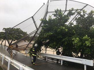 暴風で倒れた南風原中学校グラウンドのバックネット=29日午後3時46分、南風原町兼城