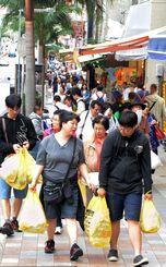 買い物袋を下げた外国人観光客でにぎわう那覇市の国際通り=2017年5月