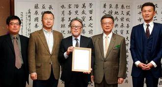 情報特区の認定事業者に初めて認定されたオキットの北村代表(中央)ら=3日、沖縄県庁