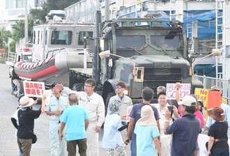 本部港に入ろうとする米軍車両を止める市民ら=17日午前7時すぎ、本部町