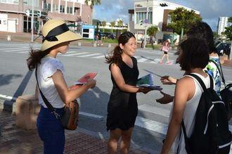 安保関連法案に反対する集会への参加を呼び掛けるチラシを配るシールズ琉球のメンバー=20日、北谷町美浜