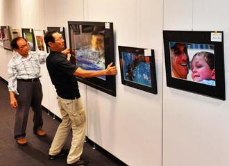 沖縄写真連盟展に向け、作品の設置作業を行うスタッフ=6日午後、タイムスギャラリー