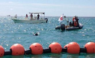 名護市辺野古沖の臨時制限区域内で、調査のため沖縄県の船から海に入り海中を確認する潜水士=31日午前10時、名護市辺野古沖