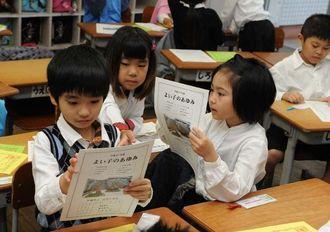 修了式後に手渡されたよい子のあゆみを眺める児童たち=24日午前10時ごろ、沖縄市・山内小学校