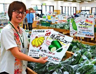 制作したポップ広告を手に「今後も地元の特産品を紹介したい」と話す古波倉夏実さん=5日、読谷村喜名・JAおきなわ読谷ファーマーズマーケット「ゆんた市場」