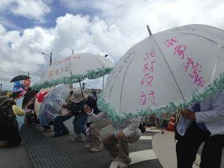 持参した雨傘にメッセージを書き込み、約570人で米軍キャンプ・シュワブを包囲する市民ら=18日午前11時半