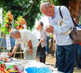 戦没者の冥福を祈り、手を合わせる参列者=21日、ミンダナオ島・ダバオ「沖縄の塔」(我喜屋あかね撮影)