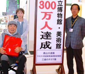 300万人目の入館者となった(左から)江口洋さん、智英子さん夫妻と安里進館長=県立博物館・美術館