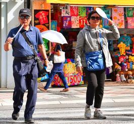 うちわや日傘で日差しを避けて歩く人たち=30日午後4時すぎ、那覇市・国際通り