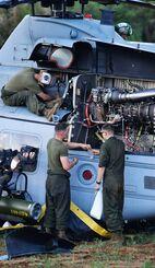 不時着したUH1ヘリのメンテナンス作業をする米兵=3日午後6時57分、うるま市津堅島(下地広也撮影)