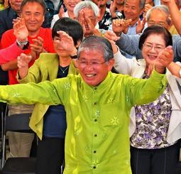 激戦の1区で当確を決め、支持者とカチャーシーを踊る赤嶺政賢さん=22日午後11時すぎ、那覇市おもろまちの選挙事務所