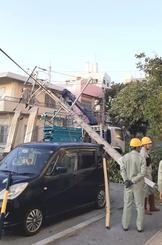 クレーンが電線に引っ掛かり電柱が倒壊した事故現場=18日午後6時、那覇市通堂町